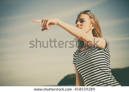 Young blonde woman casual style pointing with finger on sky background