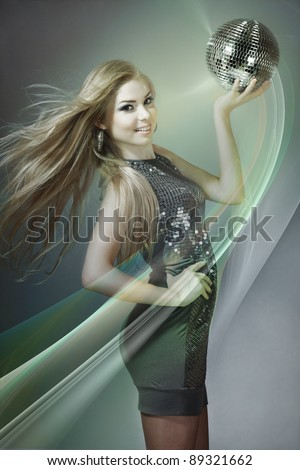 Young blonde woman dancing with disco ball - stock photo