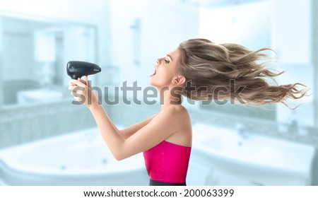 Young blonde woman drying her long hair with electric fan - stock photo