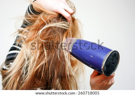 Young blonde woman drying long hair with electric fan. Fan in focus - stock photo