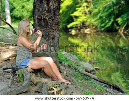 Young blonde woman fishing on creek bank
