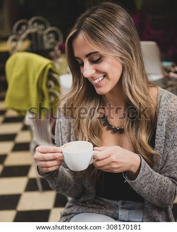 Young blonde woman having a coffee at the city - stock photo