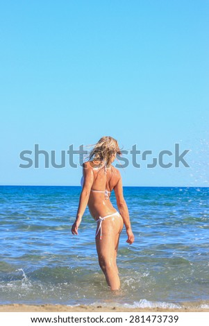 Young blonde woman having fun in the sea - Motion blur - stock photo