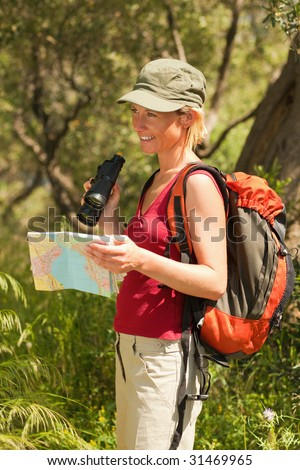 young blonde woman hiking and holding binoculars and map. - stock photo