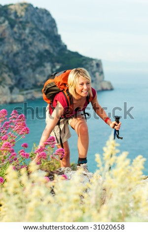 young blonde woman hiking and smiling. Copy space - stock photo