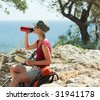 young blonde woman hiking sitting on a rock and drinking water. - stock photo
