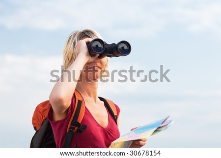 young blonde woman hiking watching through binoculars. Copy space - stock photo