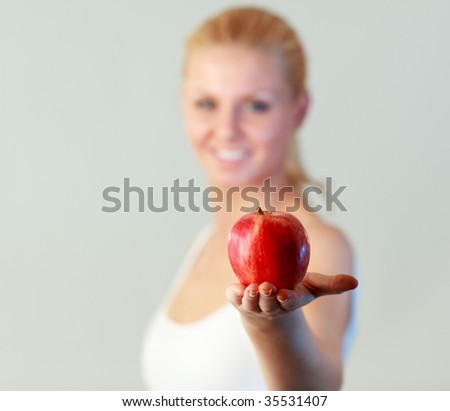 Young blonde woman holding an apple with focus on apple