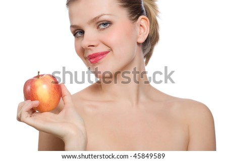 young blonde woman holding and looking at a red apple