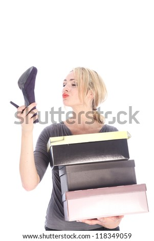 Young blonde woman holding three shoe boxes holding a high heel - stock photo