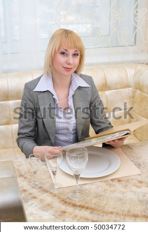 young blonde woman holds menu at first class restaurant - stock photo