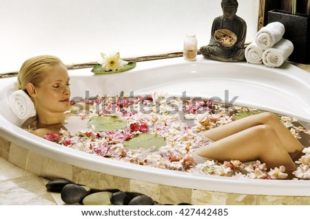 Young blonde woman in bath with rose petals - stock photo