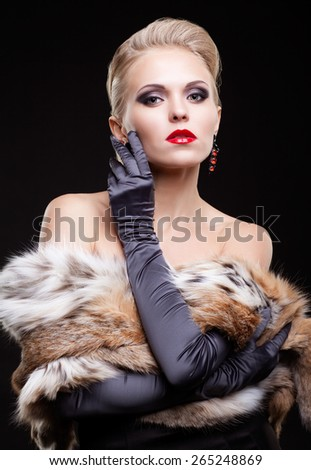 Young blonde woman in black dress and lynx fur with and long gloves on dark background