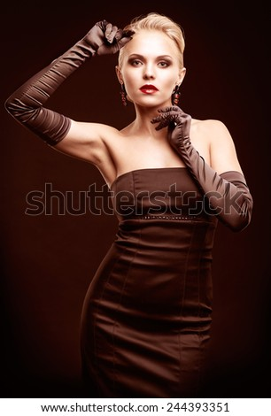 Young blonde woman in black dress toned in marsala color - stock photo