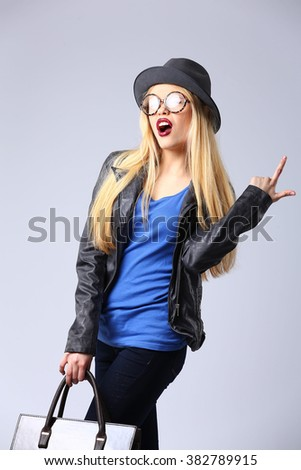 young blonde woman in casual clothes, black leather jacket, hat, glasses and blue shirt, bag, wearing boots on a high platform . studio shot.