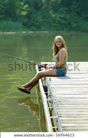 Young blonde woman in denim shorts fishing from river dock - stock photo