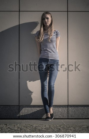 Young blonde woman in full length casual style against stone grunge wall - stock photo