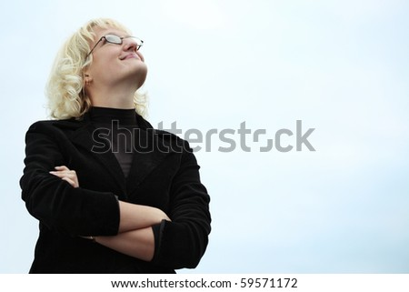 Young blonde woman in glasses looking to sky - stock photo