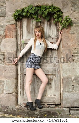 Young blonde woman in old doorway - stock photo