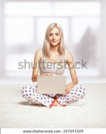 Young blonde woman in pyjamas sitting on white whole-floor carpet browsing laptop  near window - stock photo