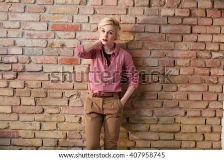 Young blonde woman in retro style standing over brick wall.