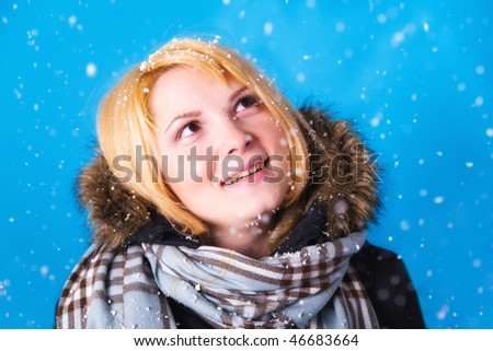 Young blonde woman in winter snowfall in studio.