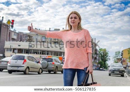 Young blonde woman is catching taxi on the street