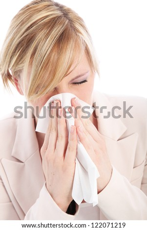Young blonde woman is suffering from a cold or flu and is sneezing into a tissue. Studio portrait over white - stock photo