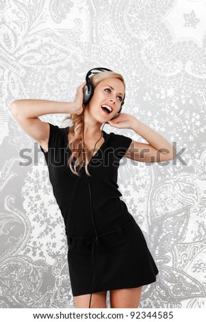 Young blonde woman listening music in headphones