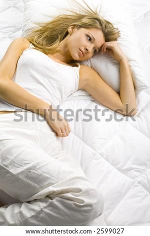 Young blonde woman lying alone in the bed. Looks dreamy. - stock photo