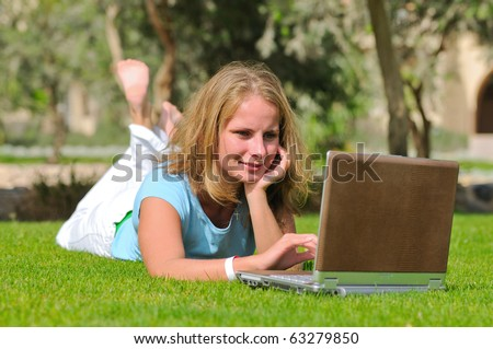 Young blonde woman lying on the grass field with laptop