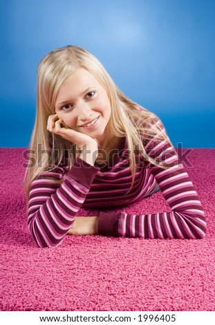 young blonde woman lying on the pink carpet (blue background) - stock photo