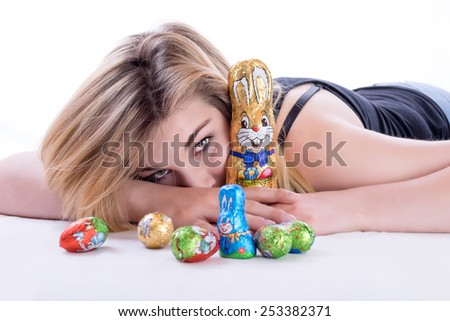 Young blonde woman lying with a lot of Easter goodies on the bed, with a chocolate rabbit in her arm - stock photo