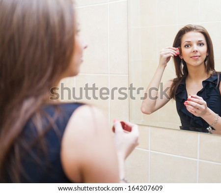 Young blonde woman makes up in front of window - stock photo
