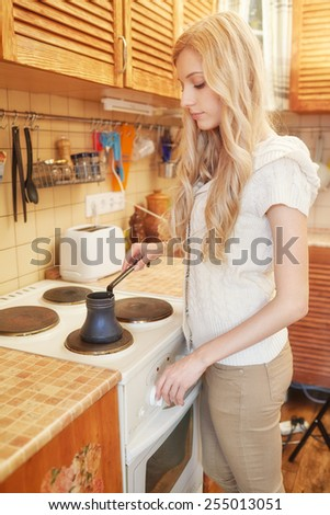 Young blonde woman making coffee electric oven in the kitchen