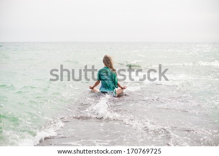 Young blonde woman meditation at the sea - stock photo