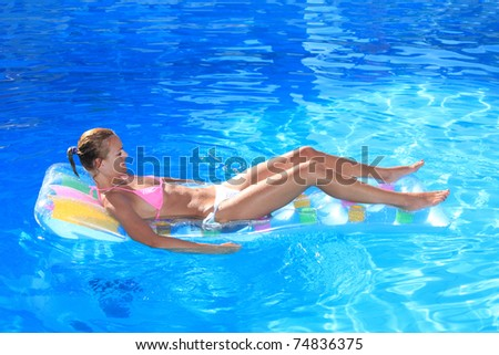 Young blonde woman on an air mattress  in the swimming pool in greece