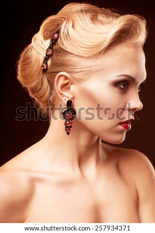 Young blonde woman on dark background toned in marsala color - stock photo