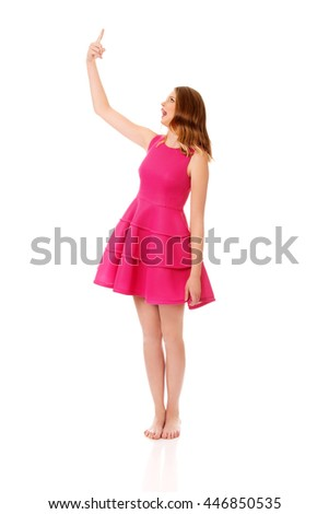 Young blonde woman pointing up - stock photo