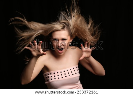 Young blonde woman posing.Isolated on dark background. - stock photo