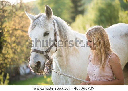 Young blonde woman posing outdoor with white horse.  - stock photo
