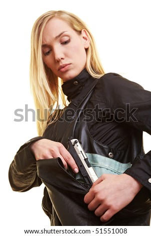 Young blonde woman pulling a pistol out of her handbag - stock photo