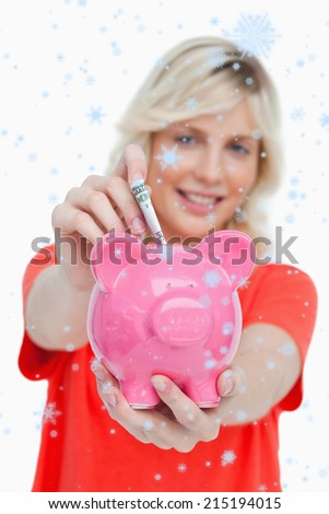 Young blonde woman putting notes into a pink piggy bank against snow falling - stock photo