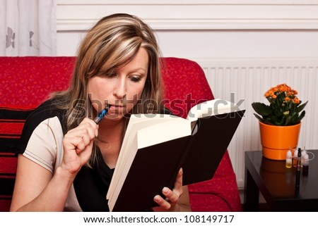 Young blonde woman reading a book, and evaporated to an electric cigarette