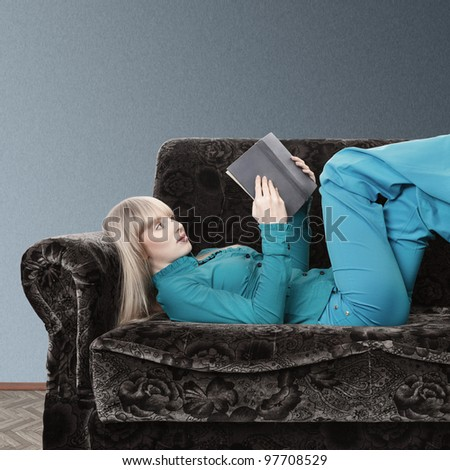 Young blonde woman reading book lying on sofa - stock photo