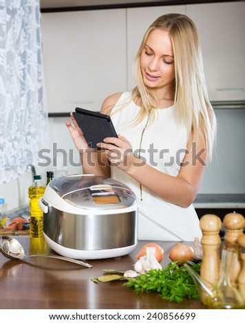 Young blonde woman reading ereader while with new electric multicooker doing food at home  - stock photo