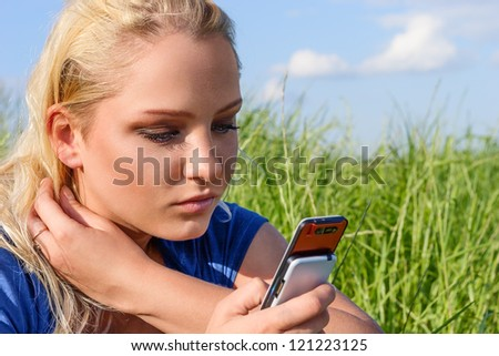 Young blonde woman reading sms on mobile phone
