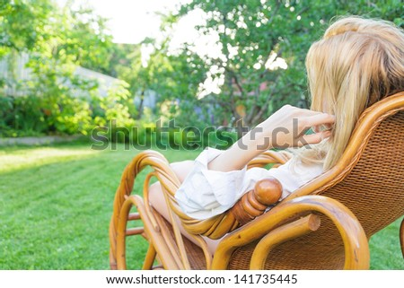 Young blonde woman relax at outdoor sitting in a rocking chair - stock photo