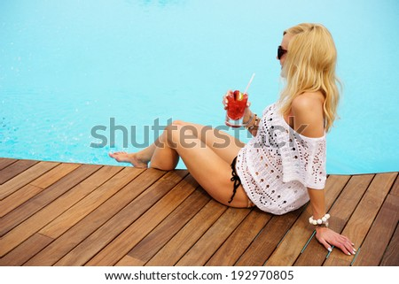 young blonde woman relaxing at the pool wearing sunglasses - stock photo
