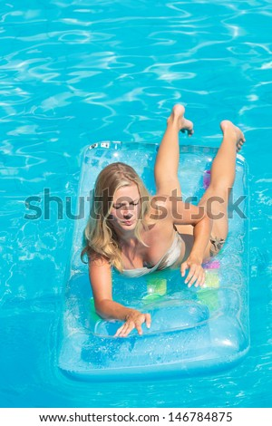 Young blonde woman relaxing at the swimming pool